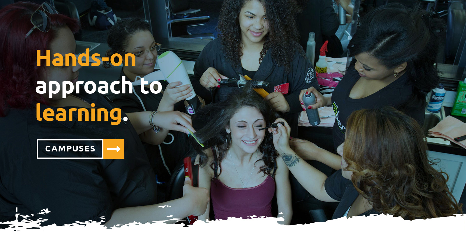 "Group of young female salon students doing makup and hair on another student with the words ""Learning here is hands-on"" over the image"